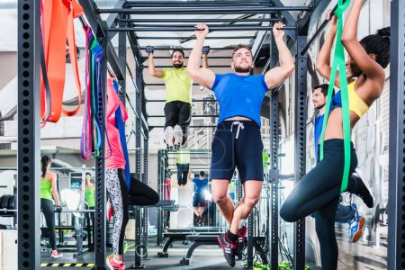 Group of women and men in cage at fitness sport exercise