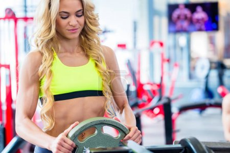 Woman taking weights from stand in fitness gym