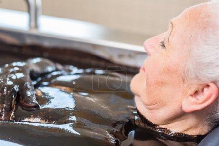 Senior woman enjoying mud bath