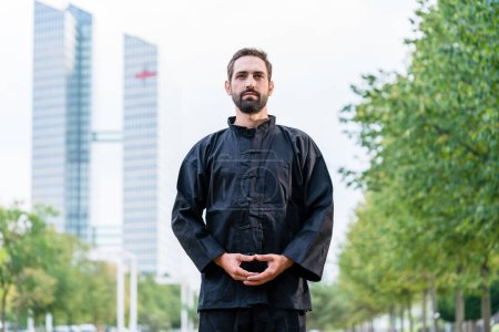 Photo for Man meditating doing martial arts in city - Royalty Free Image