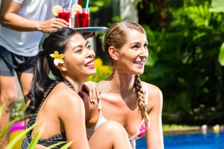 Women in vacation at Asian hotel pool with cocktails