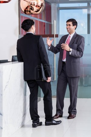 Manager and affiliate leaning at front desk of office