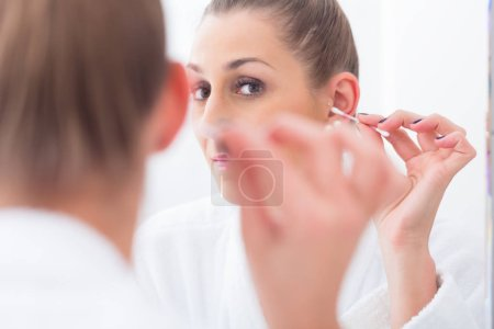 Woman cleaning her ears with cotton bud
