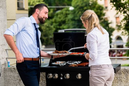 Office colleagues grilling sausages at bbq after work