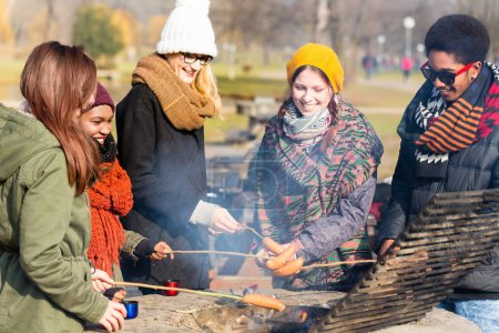 people roasting sausages outdoors