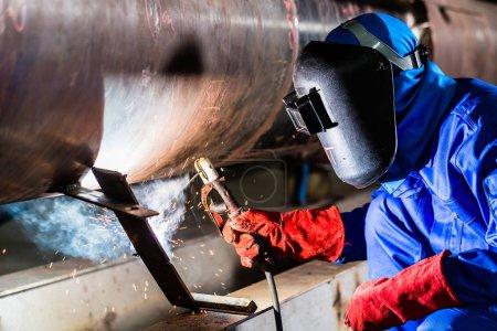 Welder in factory welding metal pipes