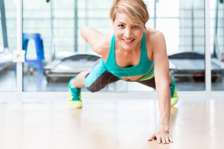 Smiling young woman doing one arm pushup in gym
