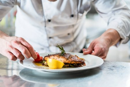 Photo for Chef with diligence finishing dish on plate, fish with vegetables - Royalty Free Image