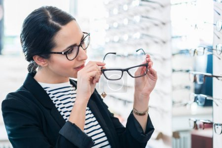 Woman taking glasses off shelf