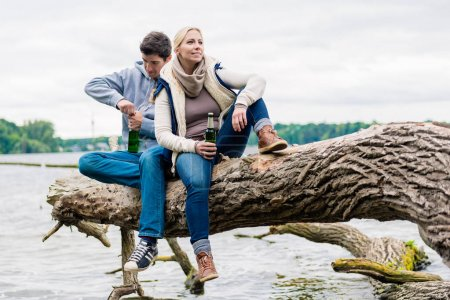 Man and woman sitting on trunk near  lakeside drinking beer