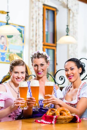 Group of people with wheat beer in Bavarian pub