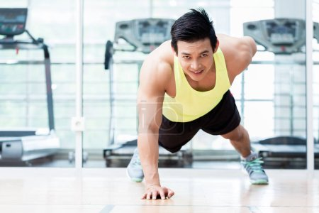 Muscular young man doing one armed pushups in gym