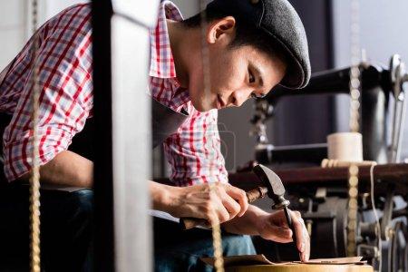 Asian shoe or belt maker in his leather workshop