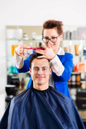 Hairdresser cutting man hair in barbershop