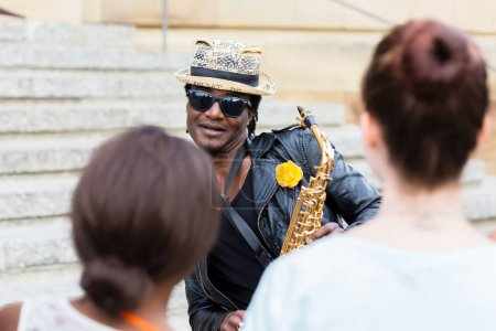 Black Street musician with sunglasses and saxophone making music