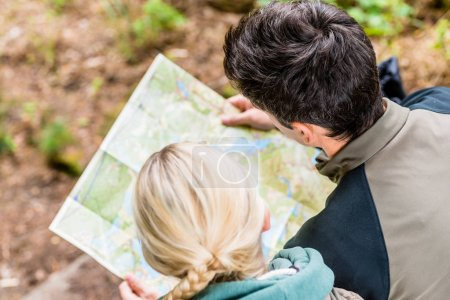 Hikers bending over trail map