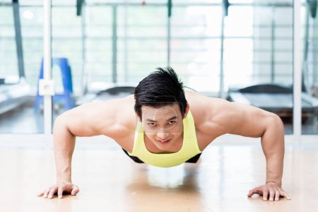 Muscular Asian man doing pushups in gym