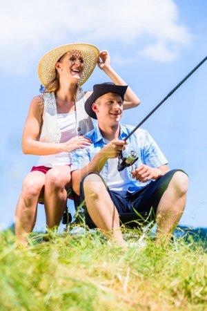 Man with fishing rod angling at lake enjoying hug