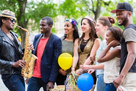 Street artist playing saxophone for multi-ethnic party group
