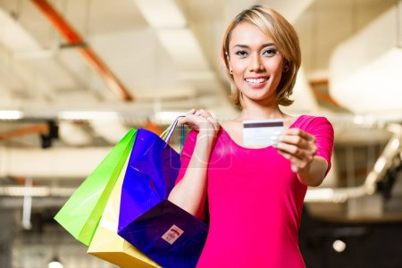 Asian young woman paying with credit card