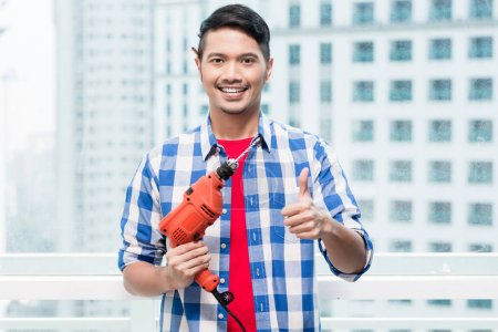 Young indonesian man with power drill