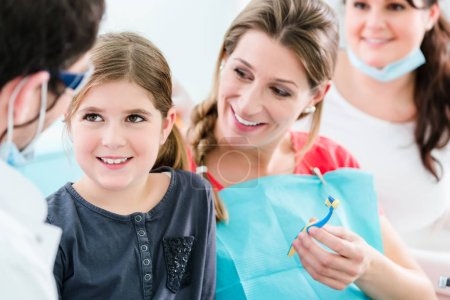 Dentist with pregnant woman and child