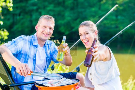 Couple of woman and man having bbq after sport fishing