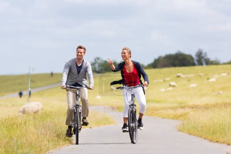 Couple having sea coast bicycle tour at levee