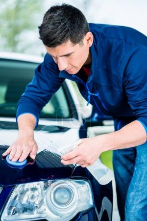 young man waxing car