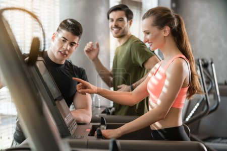 young woman increasing speed of treadmill