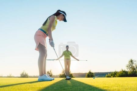 Low-angle side view of fit woman playing golf with partner