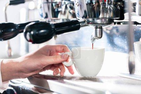 Close-up of female hand holding mug on automatic coffee machine