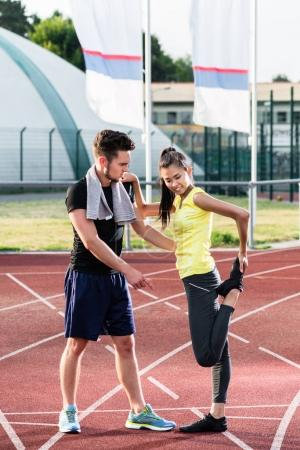 Man and woman on track of sports arena doing stretching exercises