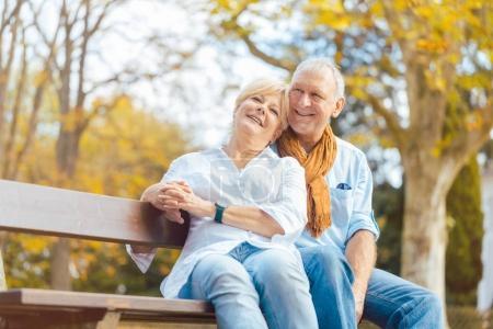 senior woman and man sitting on bench