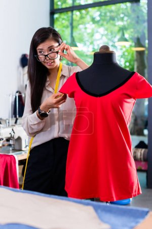 Asian tailor adjusts garment design on mannequin in her workshop