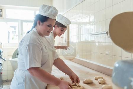 Photo pour Femmes en boulangerie formant la pâte crue pour bretzels dans la cuisine - image libre de droit