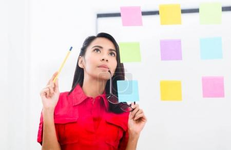Portrait of young asian employee looking at multiple reminders