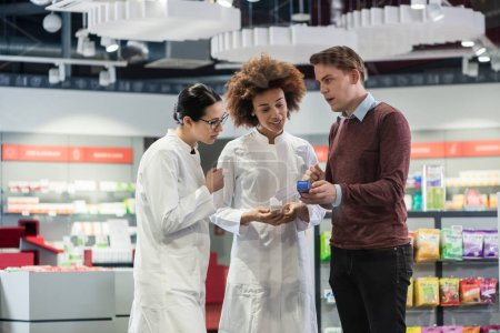 Young man asking two experienced female pharmacists