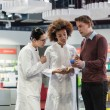 Постер, плакат: Young man asking two experienced female pharmacists