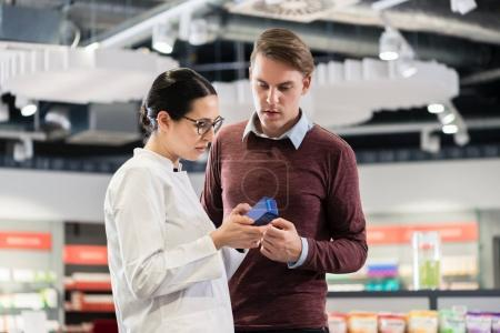 Experienced female pharmacist helping young male customer