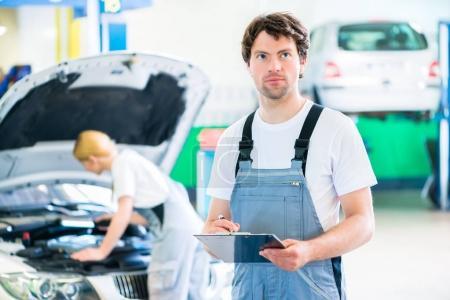 Photo pour Équipe de mécaniciens masculins et féminins examinent le moteur de voiture avec lumière et check-list en atelier - image libre de droit