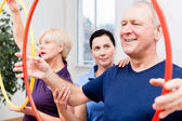 Senior couple in physiotherapy doing exercise with hula hoop
