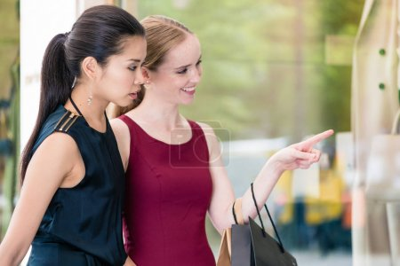 Two female best friends looking at the latest fashion trends whi