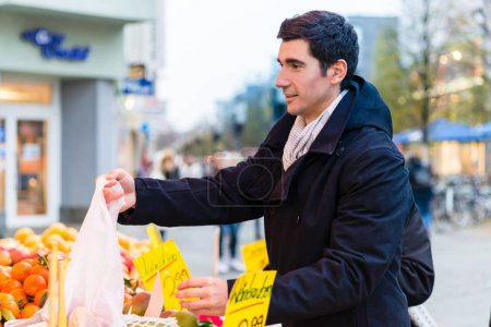 Man buying groceries on farmers market stand