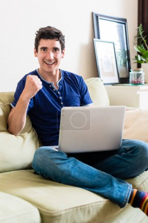 Young man looking at camera as a winner while using a laptop