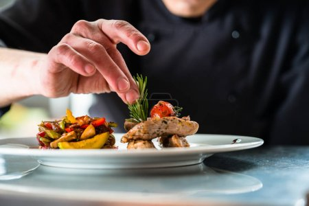 Photo for Chef finishing and garnishing food he prepared, a dish with pork meat and vegetables - Royalty Free Image