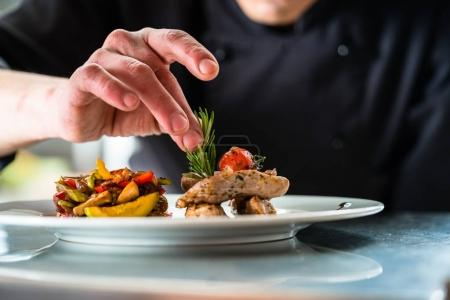 Chef finishing and garnishing food he prepared