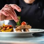 Chef finishing and garnishing food he prepared, a ...