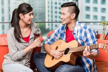 After moving together young man plays love song for his girlfrie