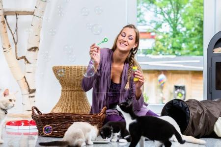 Photo pour Femme heureuse soufflant des bulles alors que le lait de consommation sont mignons chatons - image libre de droit